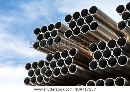 Aluminium tubes arranged in a row against the blue sky. - stock photo