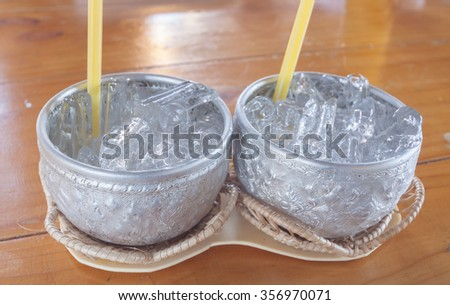 Aluminum bowl with ice cubes on wooden table - stock photo