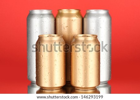 Aluminum cans with water drops on color background