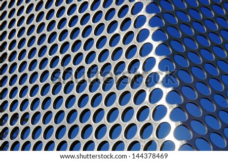 Aluminum perforated grid against a blue sky under sun light - stock photo