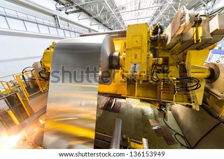 Aluminum sheet is wound on a roll on a special machine - stock photo