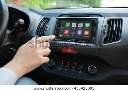Alushta, Russia - May 31, 2016: Man hand touching to the home screen multimedia system with Car Play. Car Play was created and developed by the Apple inc.