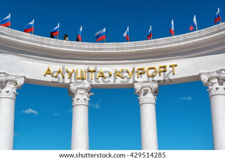 "ALUSHTA, RUSSIA - MAY 15, 2016: The rotunda ""Alushta resort"" with russian flags at the promenade in the city of Alushta. Alushta is a famous resort in Crimea. - stock photo"