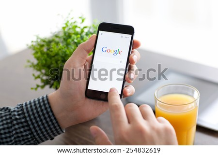 Alushta, Russia - November 21, 2014: Man holding a iPhone 6 Space Gray with social networking service Google on the screen. iPhone 6 was created and developed by the Apple inc. - stock photo