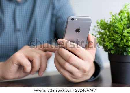 Alushta, Russia - November 20, 2014: Man holding in the hand a new iPhone 6 Space Gray. iPhone 6 was created and developed by the Apple inc. - stock photo