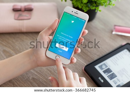 Alushta, Russia - November 5, 2015: Woman holding a iPhone 6S Rose Gold with social networking service Twitter on the screen. iPhone 6S was created and developed by the Apple inc. - stock photo
