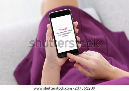 Alushta, Russia - November 22, 2014: Woman holding a iPhone 6 Space Gray with social Internet service Pinterest on the screen. iPhone 6 was created and developed by the Apple inc. - stock photo