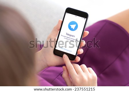 Alushta, Russia - November 22, 2014: Woman holding a iPhone 6 Space Gray with social networking service Telegram on the screen. iPhone 6 was created and developed by the Apple inc. - stock photo