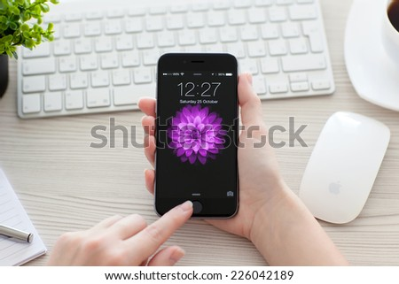 Alushta, Russia - October 25, 2014: Girl unlock her phone iPhone 6 Space Gray over the table. iPhone 6 was created and developed by the Apple inc. - stock photo