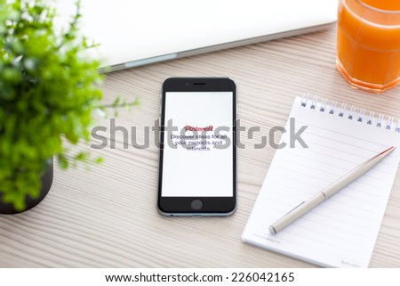 Alushta, Russia - October 24, 2014: Phone iPhone 6 Space Gray on the table with social Internet service Pinterest on the screen. iPhone 6 was created and developed by the Apple inc.  - stock photo