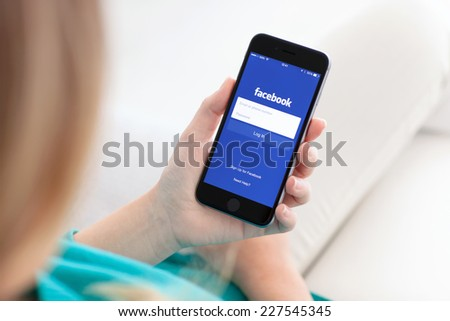 Alushta, Russia - October 29, 2014: Woman holding a iPhone 6 Space Gray with social networking service Facebook on the screen. iPhone 6 was created and developed by the Apple inc. - stock photo