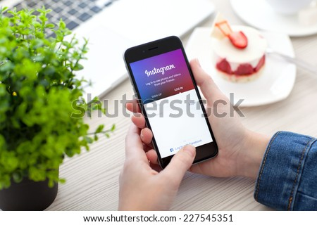 Alushta, Russia - October 28, 2014: Woman holding a iPhone 6 Space Gray with social networking service Instagram on the screen. iPhone 6 was created and developed by the Apple inc.  - stock photo