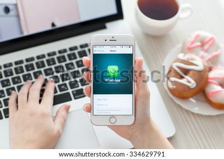 Alushta, Russia - October 29, 2015: Woman holding iPhone6S Rose Gold with social networking service WhatsApp on the screen. iPhone 6S Rose Gold was created and developed by the Apple inc. - stock photo