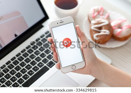 Alushta, Russia - October 29, 2015: Woman holding iPhone6S Rose Gold with social networking service Google Plus on the screen. iPhone 6S Rose Gold was created and developed by the Apple inc. - stock photo