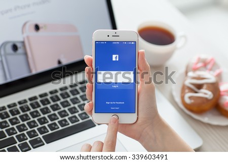 Alushta, Russia - October 29, 2015: Woman holding iPhone6S Rose Gold with social networking service Facebook on the screen. iPhone 6S Rose Gold was created and developed by the Apple inc. - stock photo