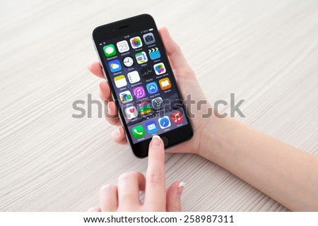 Alushta, Russia - October 23, 2014: Woman holding new phone iPhone 6 Space Gray over the table. iPhone 6 was created and developed by the Apple inc. - stock photo