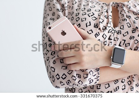Alushta, Russia - October 22, 2015: Woman with Apple Watch in the hand holding iPhone 6 S Rose Gold. iPhone 6S and Watch was created and developed by the Apple inc. - stock photo