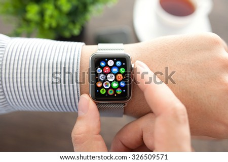 Alushta, Russia - September 1, 2015: Man hand with Apple Watch and app Icon on the screen. Apple Watch was created and developed by the Apple inc. - stock photo
