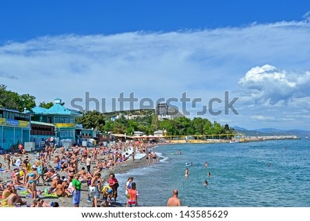 ALUSHTA, UKRAINE - JUN 01: People on the public pebble beach near Black Sea in Alushta, Ukraine on June 01, 2013. Alushta is famous Crimean resort. More 6,134 mln. tourists visited Crimea in 2012. - stock photo