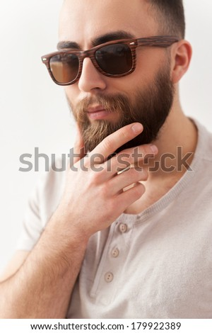 Always feeling confident. Handsome young man in sunglasses holding hand on chin and looking away
