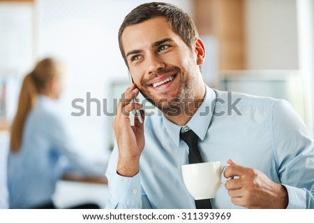 Always in good mood. Cheerful young businessman in formalwear talking on the mobile phone and holding cup of coffee while his female colleague working in the background - stock photo