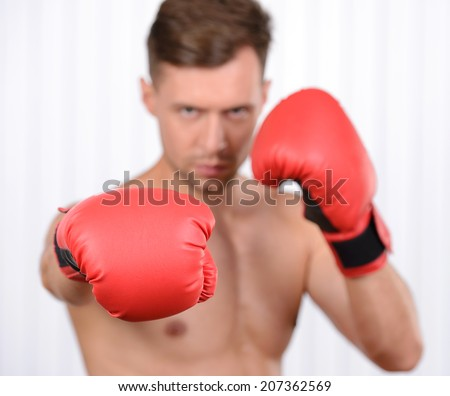 Always in great shape. Cheerful young muscular man boxer training in boxing gloves - stock photo