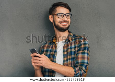 Always in touch. Cheerful young man in glasses holding his smartphone and looking away with smile while standing against grey background - stock photo