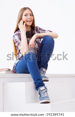 Always in touch with friends. Cute teenage girl talking on the mobile phone and smiling while sitting on staircase - stock photo
