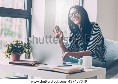 Always in touch with her friends. Cheerful young beautiful woman waving while looking at her laptop and sitting at her working place