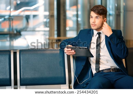 Always on the go. Portrait of handsome smiling businessman in formalwear holding a digital tablet with earphones while sitting in the airport in business lounge  - stock photo