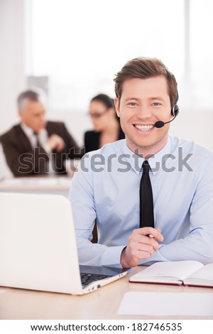 Always ready to help. Handsome young man in headset looking at camera and smiling while people working on background  - stock photo