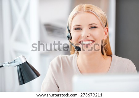 Always ready to help you. Happy young woman in headset looking at camera and smiling while sitting at her working place - stock photo