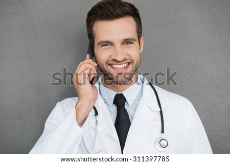 Always ready to help you. Joyful young doctor in white uniform smiling and talking on the mobile phone while standing against grey background - stock photo