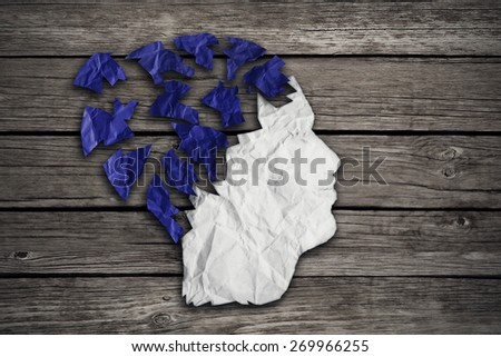 Alzheimer patient medical mental health care concept as a sheet of torn crumpled white blue paper shaped as side profile of human face on wood as a symbol for neurology and dementia or memory loss. - stock photo