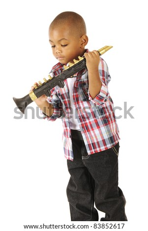 Am adorable preschooler checking the valves on his toy clarinet.  Isolated on white. - stock photo