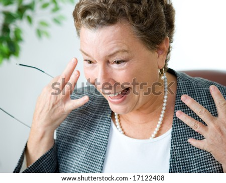 Am amazed looking businesswoman looking at something (her computer perhaps) with delight and surprise. - stock photo