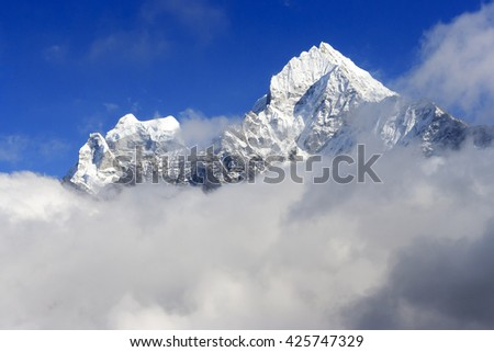 Ama Dablam in the clouds. Himalayas mountain landscape. Nepal. - stock photo