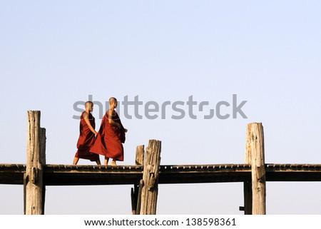 AMARAPURA, MYANMAR - CIRCA FEBRUARY 2011: Buddhist monks on U Bein bridge in Amarapura, Myanmar (Burma) circa February 2011.  U Bein bridge is the longest bridge in the world made of teak wood. - stock photo