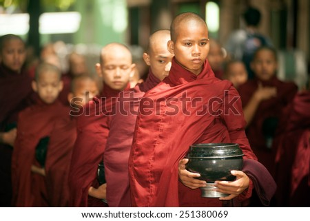 AMARAPURA, MYANMAR - JUNE 30 : Young Buddhist monks waiting in line for lunch during an Alms Ceremony at the Maha Gandayon Monastery  on June 30,2014,Mandalay Division,Central of Myanmar. - stock photo