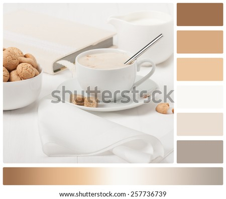 Amaretti Biscuits. Cup Of Cappuccino Coffee. Lump Demerara Sugar. Book With Handmade Textile Cover. Palette With Complimentary Colour Swatches. - stock photo