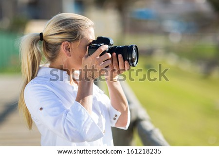 amateur middle aged photographer taking pictures outdoors - stock photo