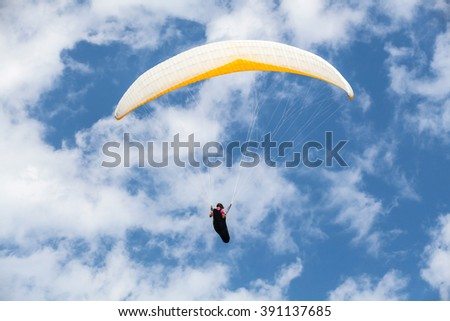Amateur paraglider in blue sky with clouds