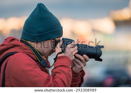 Amateur photographer is working outdoor and taking some pictures