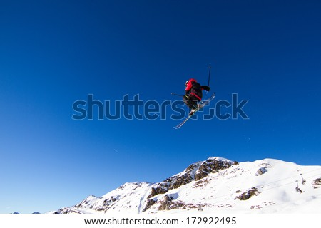 Amateur skier performing jump in snow park with blue sky in the background. Trademarks have been removed.