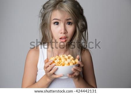 Amazed asian woman with popcorn - stock photo