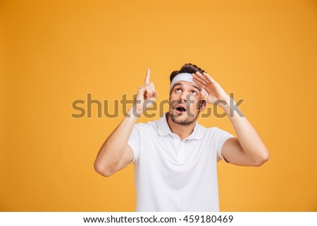 Amazed attractive young sportsman looking and pointing up over yellow background