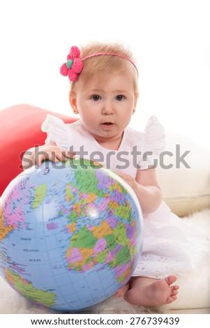 Amazed baby girl holding inflate world globe  - stock photo