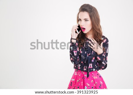 Amazed beautiful young woman talking on cell phone over white background - stock photo