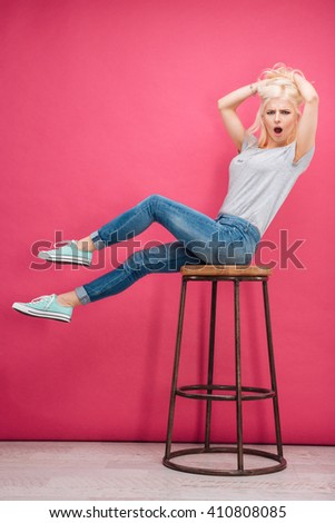 Amazed blonde woman sitting on the chair and looking at camera over pink background - stock photo