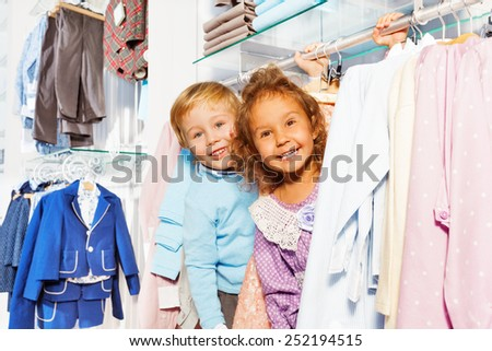 Amazed boy and girl play hide-and-seek in shop - stock photo